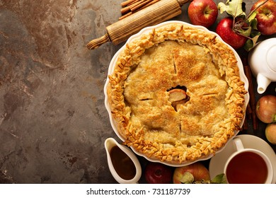 Apple pie decorated with fall leaves with caramel sauce and tea, fall baking concept overhead shot with copy space