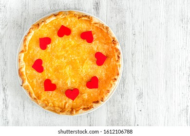Apple pie decorated with hearts for Valentine day on a white wooden background.