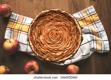 Apple pie decorated in shape of a rose flower, in a tray, on kitchen towel, surrounded by apples fruits, on vintage table. Above view of tatsy apple pie in rustic settings.