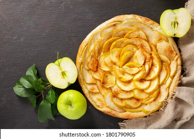 apple pie with fresh fruits on a darl background, top view