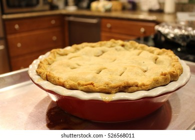 Apple pie in the kitchen in a red ceramic pie tray.