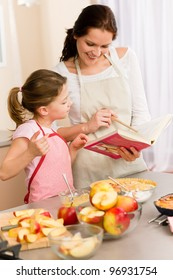 Apple pie mother and daughter follow recipe from baking cookbook