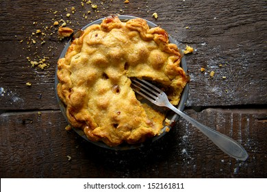 Apple Pie on a Brown Rustic Wooden Background with Fork and Crumbs