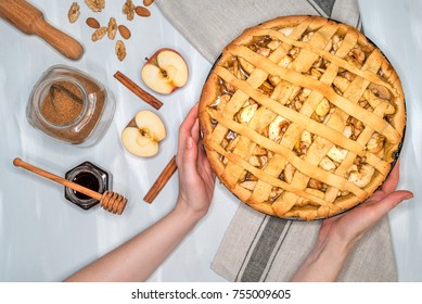 apple pie on a gray kitchen towel. Hands put on the table. Apples, cinnamon, sugar, honey and nuts, top view