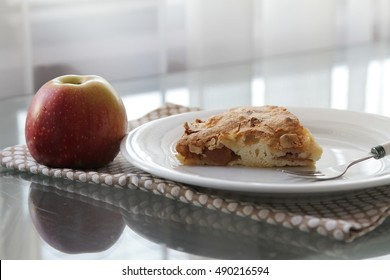 Apple pie on a plate with an apple
