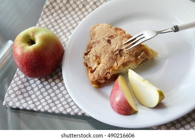 Apple pie on a plate with a few apple slices and an apple