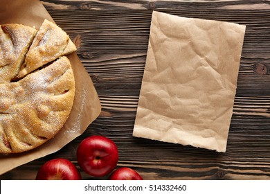 Apple pie on a wooden rustic table. Top view.  Piece kraft paper empty space for text.