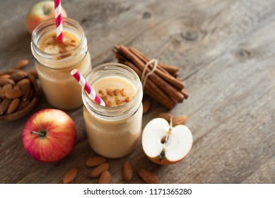 Apple pie protein smoothie drink with almond milk. Homemade apple smoothie with apple pie spices (cinnamon) on wooden background, copy space.