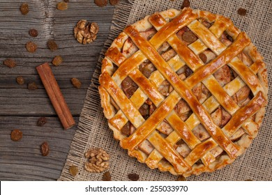 Apple pie with raisins and cinnamon on vintage wooden background texture. Top view