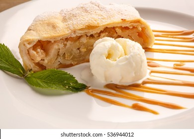 Apple pie, apple slices, ice cream and caramel  on a white plate