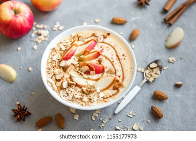 Apple Pie Smoothie Bowl. Breakfast smoothie bowl with apples, cinnamon, almond milk, oat granola, salted caramel and spices, top view.