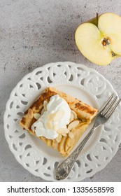 Apple pie tart, ingredients - apples and cinnamon on rustic wooden background - top view. Pie slices plated in white plates.