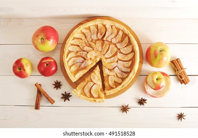 Apple pie tart, ingredients - apples and cinnamon on rustic wooden background - top view