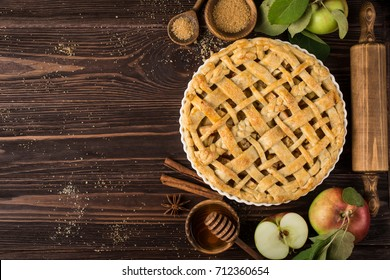 apple pies and ingredients on wooden background.  Top view.