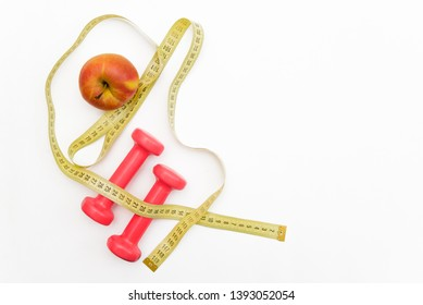 apple and pink dumbbells a healthy lifestyle for a beautiful body to lose weight and have a sports figure to cultivate the right eating habits and diet on a white background
