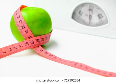 Apple with pink measuring tape and Weight  scales.Concept of health care. Selective focus