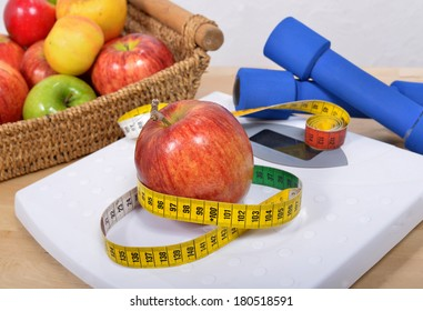 Apple placed on a scales and free weights