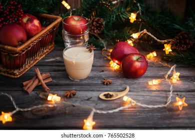 Apple puree or sauce in a small glass bowl with fresh  red apples and spices on an old wooden table