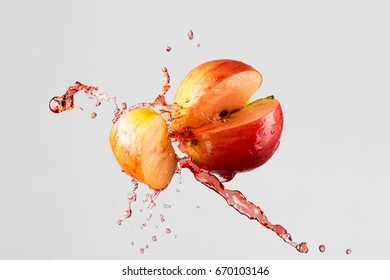 apple and red juice splash isolated on a gray background.