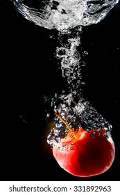 Apple Red. In water. Black background.