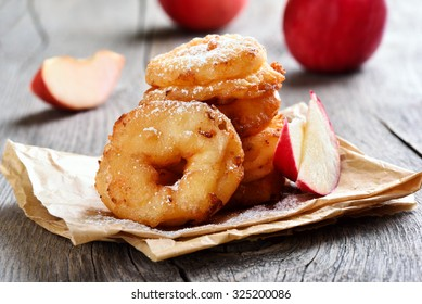 Apple rings over baking paper on rustic table