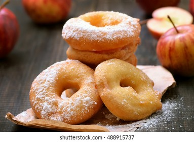 Apple rings over baking paper on wooden table, close up