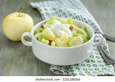 Apple salad with celery, walnuts and yoghurt on a wooden table. Waldorf salad.
