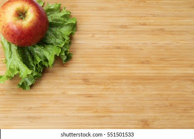 Apple and salad on wood background