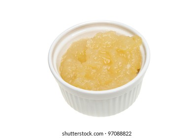 Apple sauce in a ramekin isolated against white