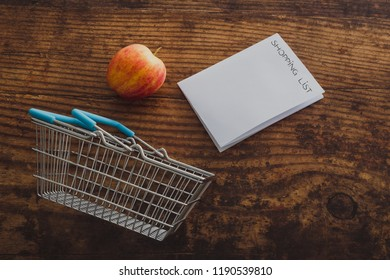 apple and shopping basket with shopping list on memo paper and wooden surface background