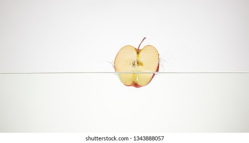 apple slice falls into the water scattering a lot of splashes and drops.