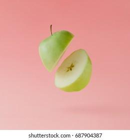 Apple sliced on pastel pink background. Minimal fruit concept.