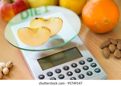 apple slices on digital kitchen scale and word diet reflected
