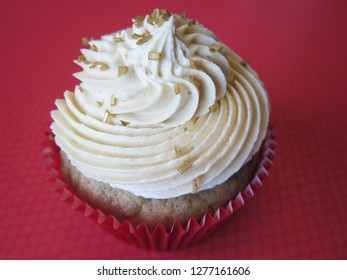 Apple spice cupcake topped with caramel whipped frosting and gold sugar garnish