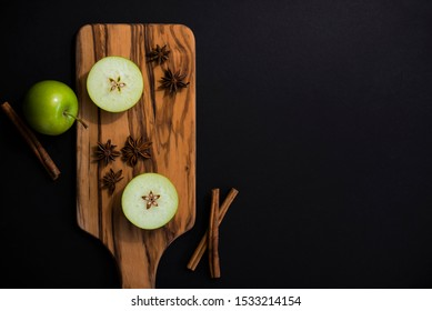 apple star with star anise, and cinnamon sticks, green apple sliced horizontal to show the core star, holiday still life, lifestyle, copyspace, copy space, recipe mulled spiced cider, holiday beverage