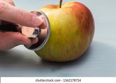Apple and stethoscope concept of the presence of nitrates and GMOs