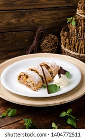Apple strudel with creamy ice cream, garnished with mint on a white plate on a short wooden background. Close-up. Space