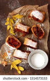 Apple strudel with fresh red apples on a wooden background