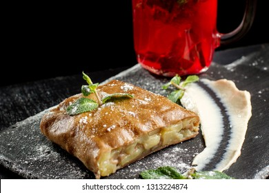 Apple strudel, garnished with mint and sprinkled with powdered sugar. Close-up on strudel, in the background is a hot drink.