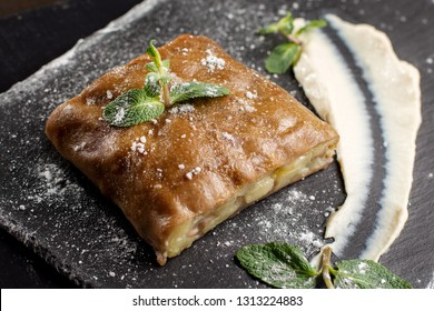 Apple strudel, garnished with mint and sprinkled with powdered sugar. Close-up on strudel.