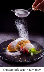 Apple strudel with icing sugar,almonds and vanilla ice cream on a concrete table