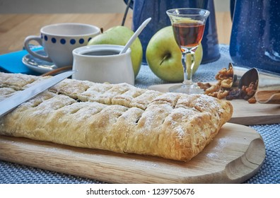 Apple strudel with nuts, raisins, cinnamon and powdered sugar. Homemade apple strudel with fresh apples. Country style apple strudel.