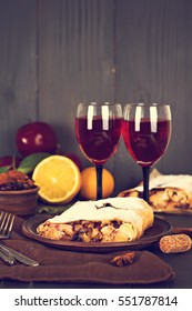 Apple strudel (pie) with dried fruits, oranges, cranberries, walnuts with sugar and mulled wine on dark background.   Lunch, dinner for two. Romantic dinner.