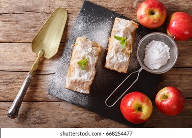 Apple strudel sprinkled with sugar powder close-up on the table. horizontal view from above