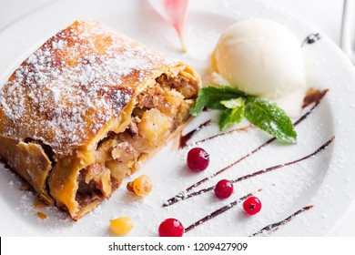 Apple strudel with vanilla ice cream and mint and berries on white plate, close up