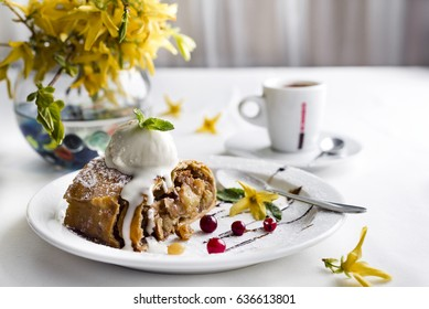 Apple strudel with vanilla ice cream and coffee, yellow flowers on a white background