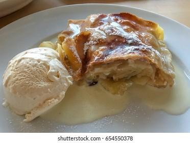 Apple strudel with vanilla sauce and vanilla ice-cream on a white dish