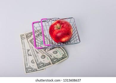 An apple in a supermarket basket. Healthy fruit. Dollars. Spending on healthy food