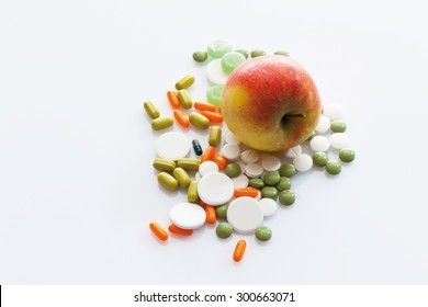 Apple with tablets on white background
