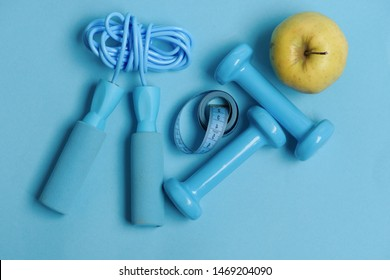 Apple, tape, dumbbells and skipping rope in cyan color on blue background. Health regime and fitness symbols. Fit shape and sport concept. Jump rope, fruit, measure tape and barbells, top view
